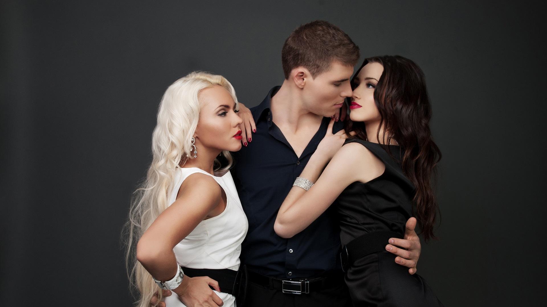 hombre-abrazando-a-dos-mujeres-vestidas-de-blanco-y-negro