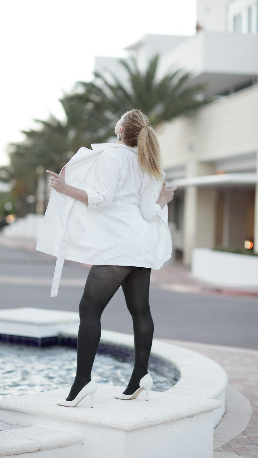 mujer-con-gabardina-blanca-y-mallas-negras-exhibiendose-encima-de-una-fuente