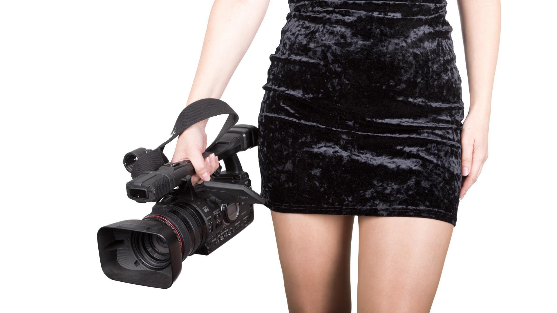 mujer-con-vestido-negro-corto-soteniendo-una-camara-de-filmacion