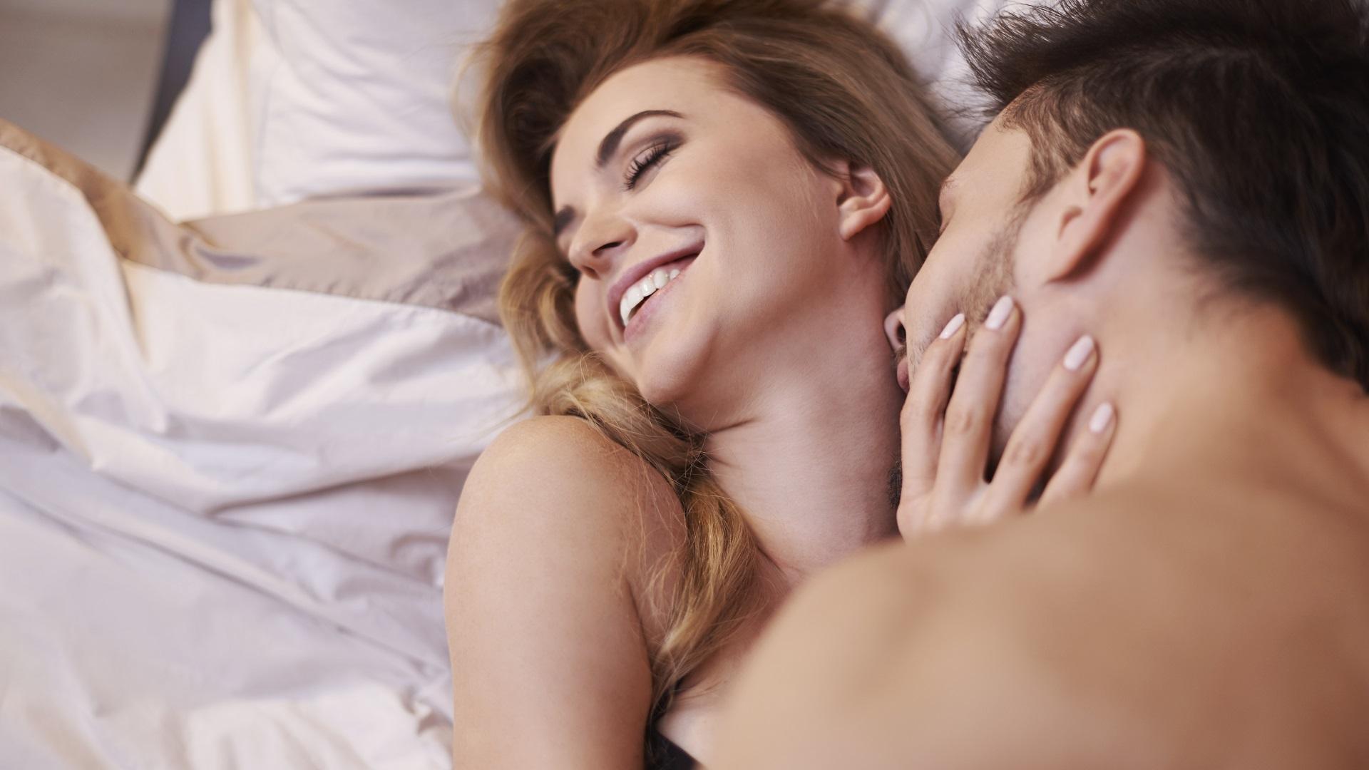 pareja-en-la-cama-mientras-el-hombre-besa-el-cuello-de-la-mujer